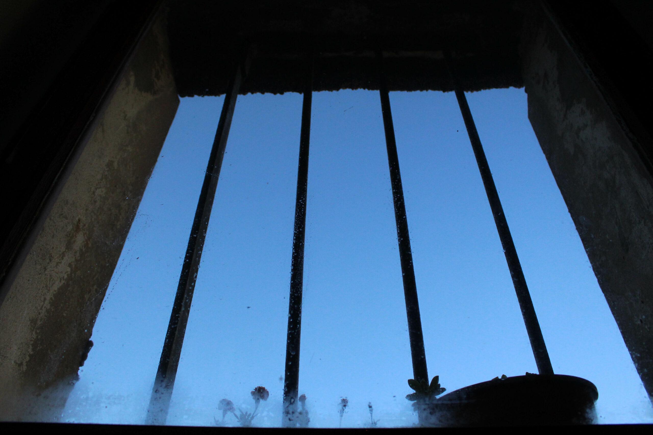 Fenêtre avec des barreaux laissant apercevoir un ciel d'un bleu intense.