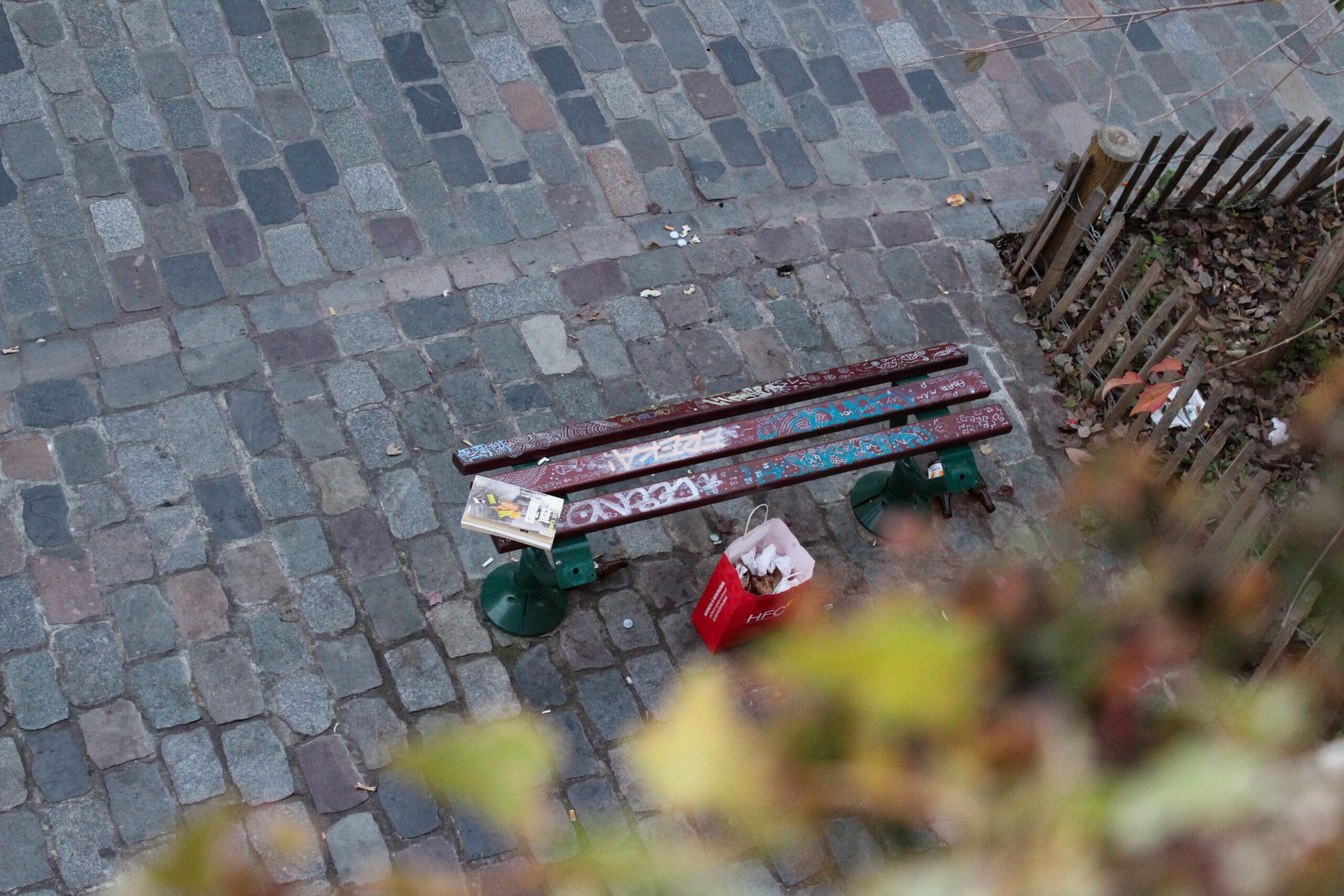 Banc rue Kléber (Bordeaux) avec graffitis et déchets laissés par des passant·es.