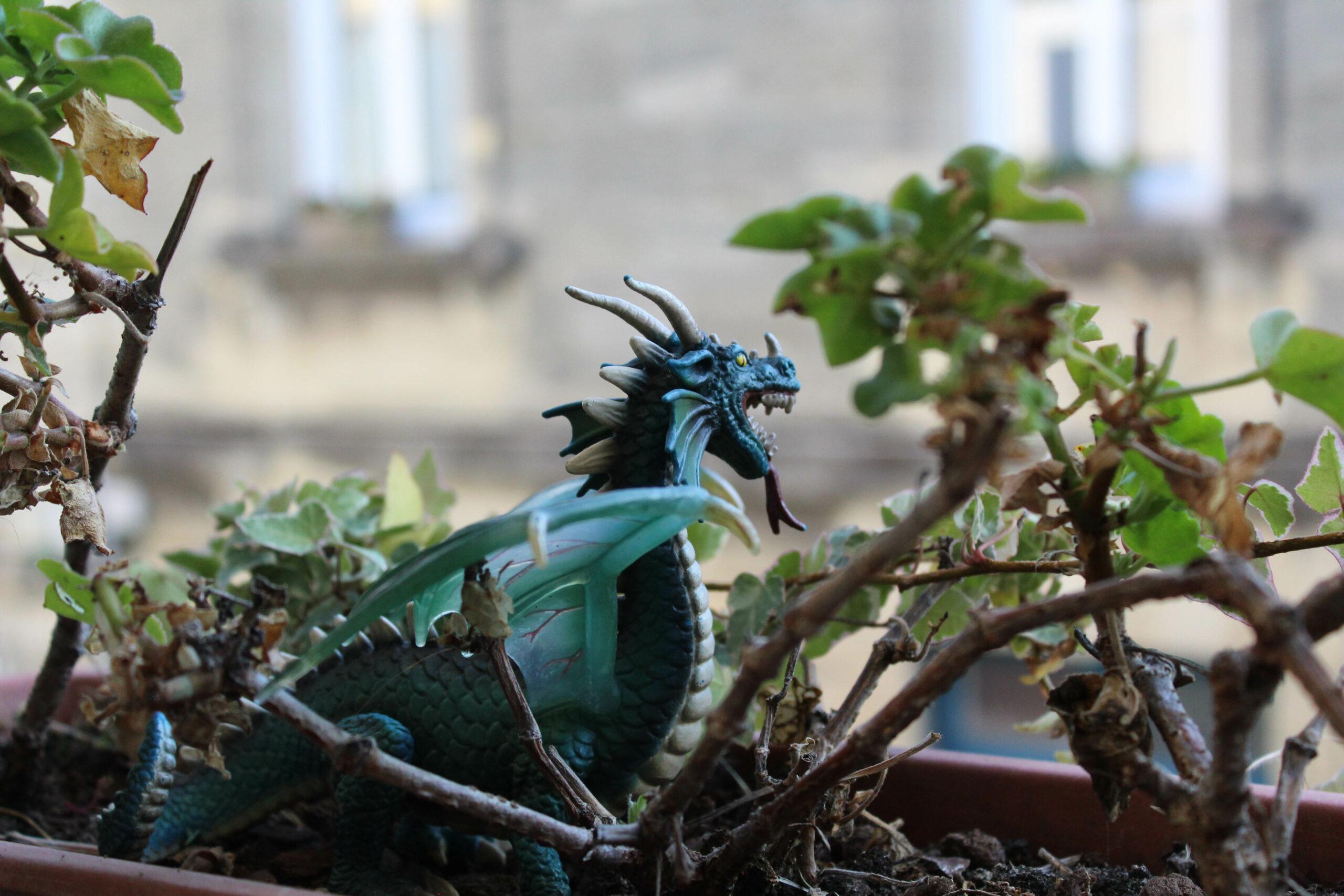 Dragon décoratif sur une jardinière où pousse du lierre.
