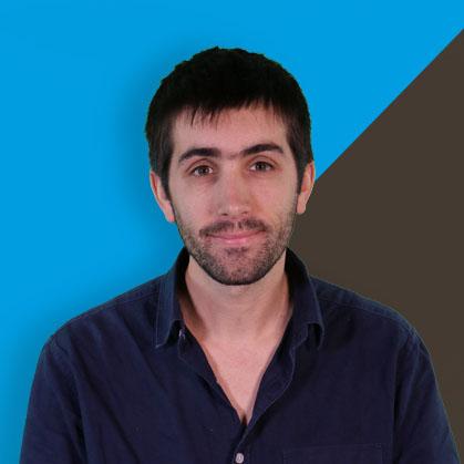 Le chercheur pose sur un fond  marron et bleu de l'université de Bordeaux.